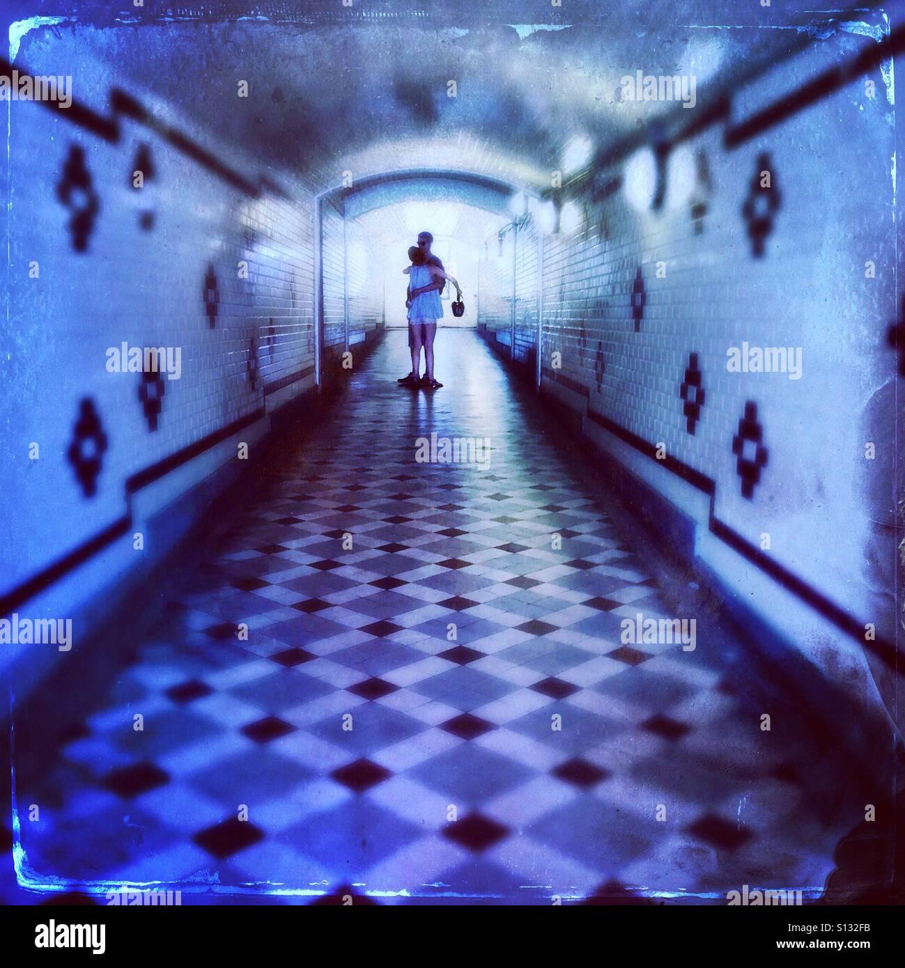 Tunnel de l'amour...un couple hugging in un tunnel pour piétons avec carreaux Art déco Banque D'Images