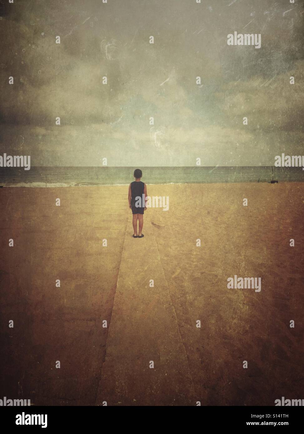 Garçon solitaire sur la plage Photo Stock