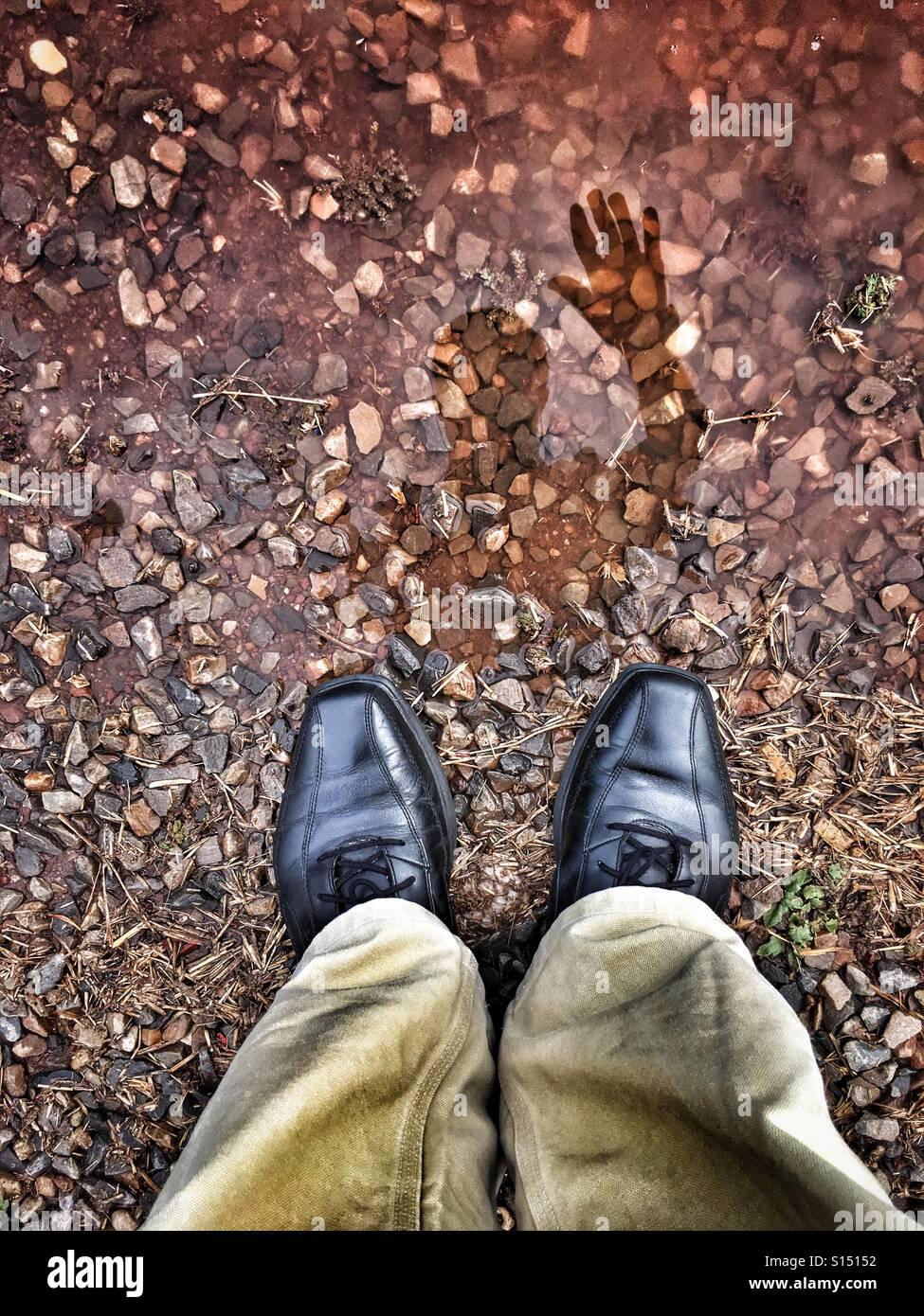 La réflexion d'un homme de tissage lui-même dans une flaque. Photo Stock