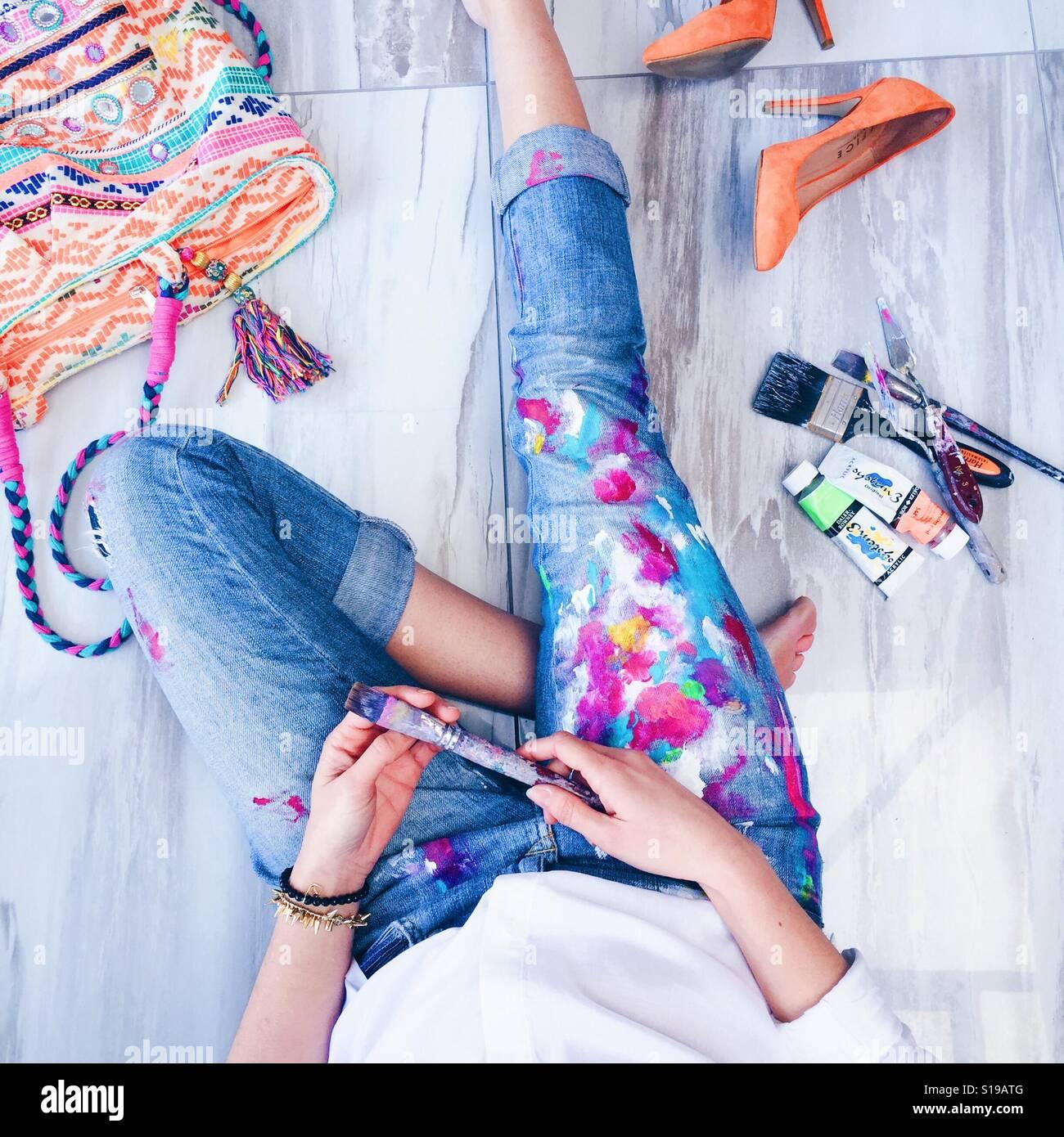 Détente de l'artiste portant des jeans bleu couvert de peinture accessoires de peinture avec des couleurs vives Banque D'Images