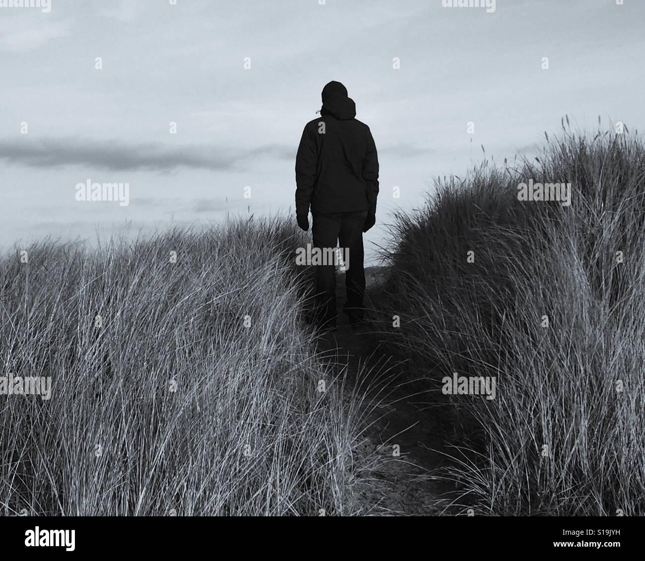 Silhouette d'un homme debout sur une piste dans les dunes de sable. Banque D'Images