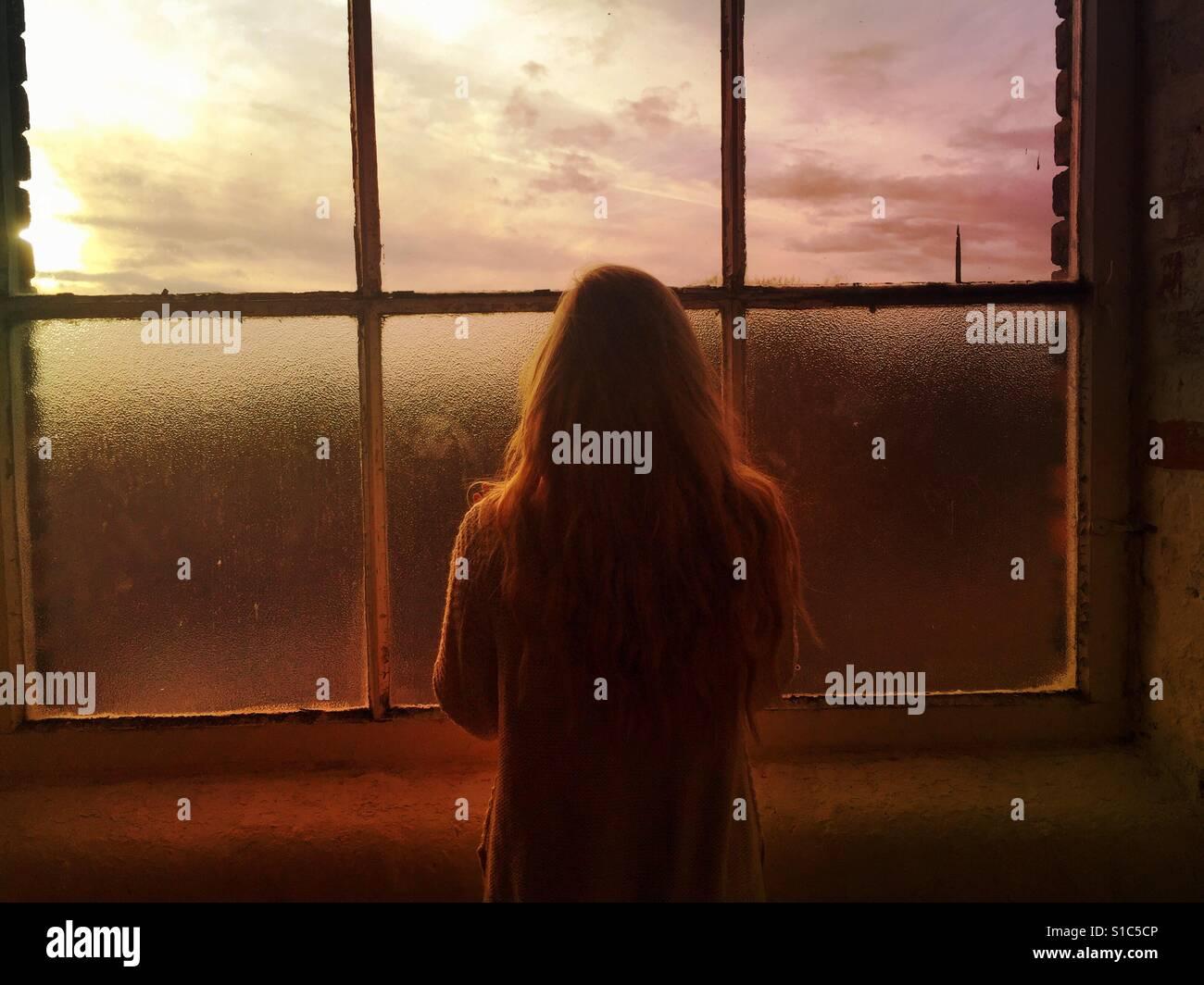 Vue arrière d'une femme seule en regardant par la fenêtre au coucher du soleil Photo Stock