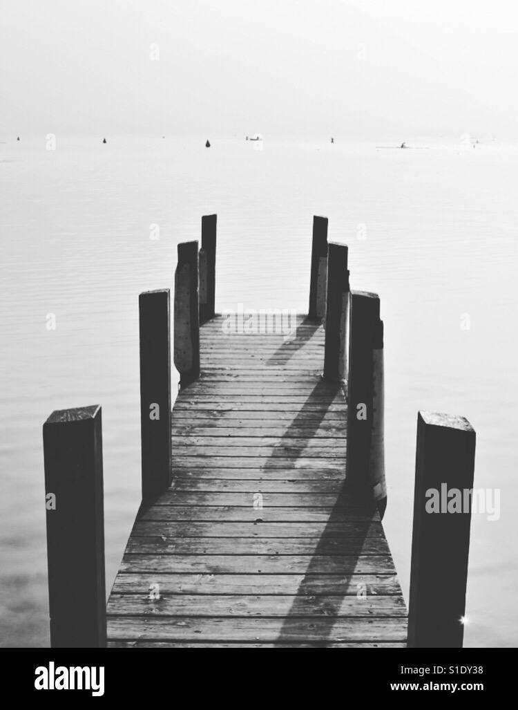 Une jetée en bois ou pier s'étend dans les eaux du lac d'Annecy, France. Photo Stock