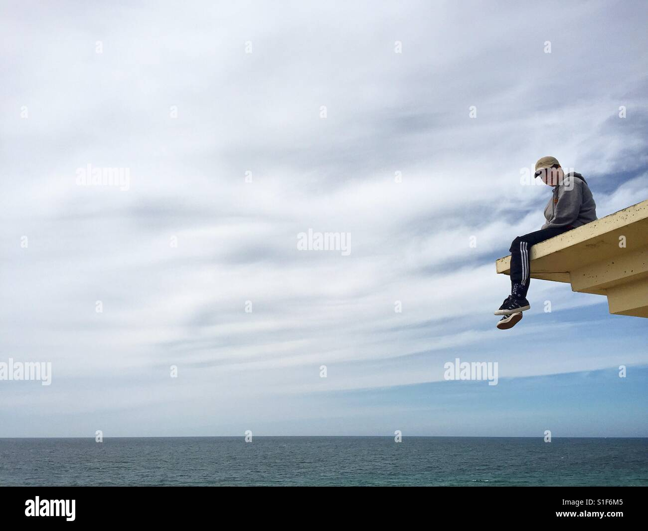 Adolescent assis sur un toit avec vue sur la mer, France. Photo Stock