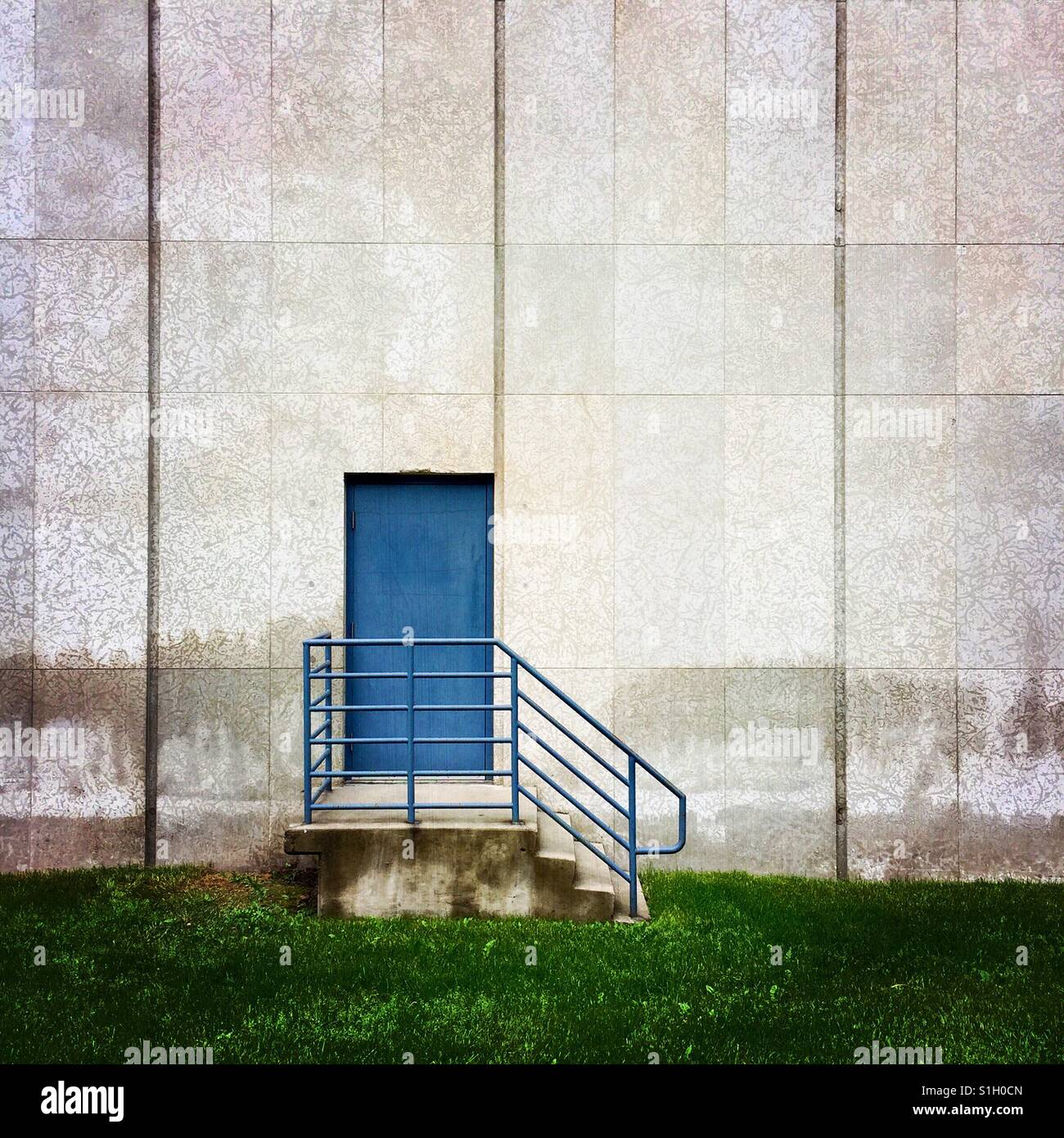 Une simple composition d'une porte bleue sur le côté d'un immeuble Banque D'Images