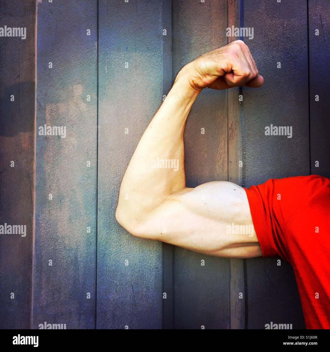 Un homme de plier le bras droit muscle biceps devant un mur sombre Photo Stock