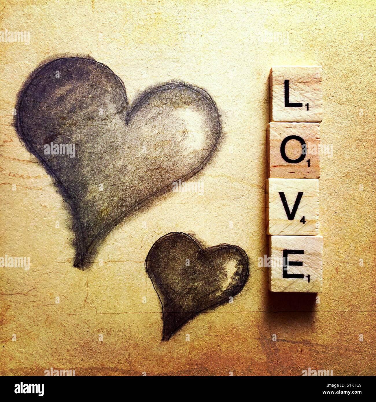 Un simple dessin au crayon de deux coeurs et le mot amour énoncées avec lettres en bois Photo Stock