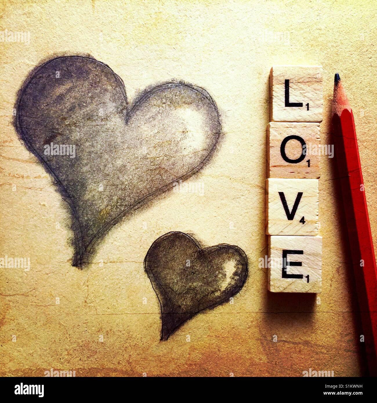 Un simple dessin au crayon de deux coeurs avec un crayon et le mot amour énoncées avec lettres en bois Photo Stock