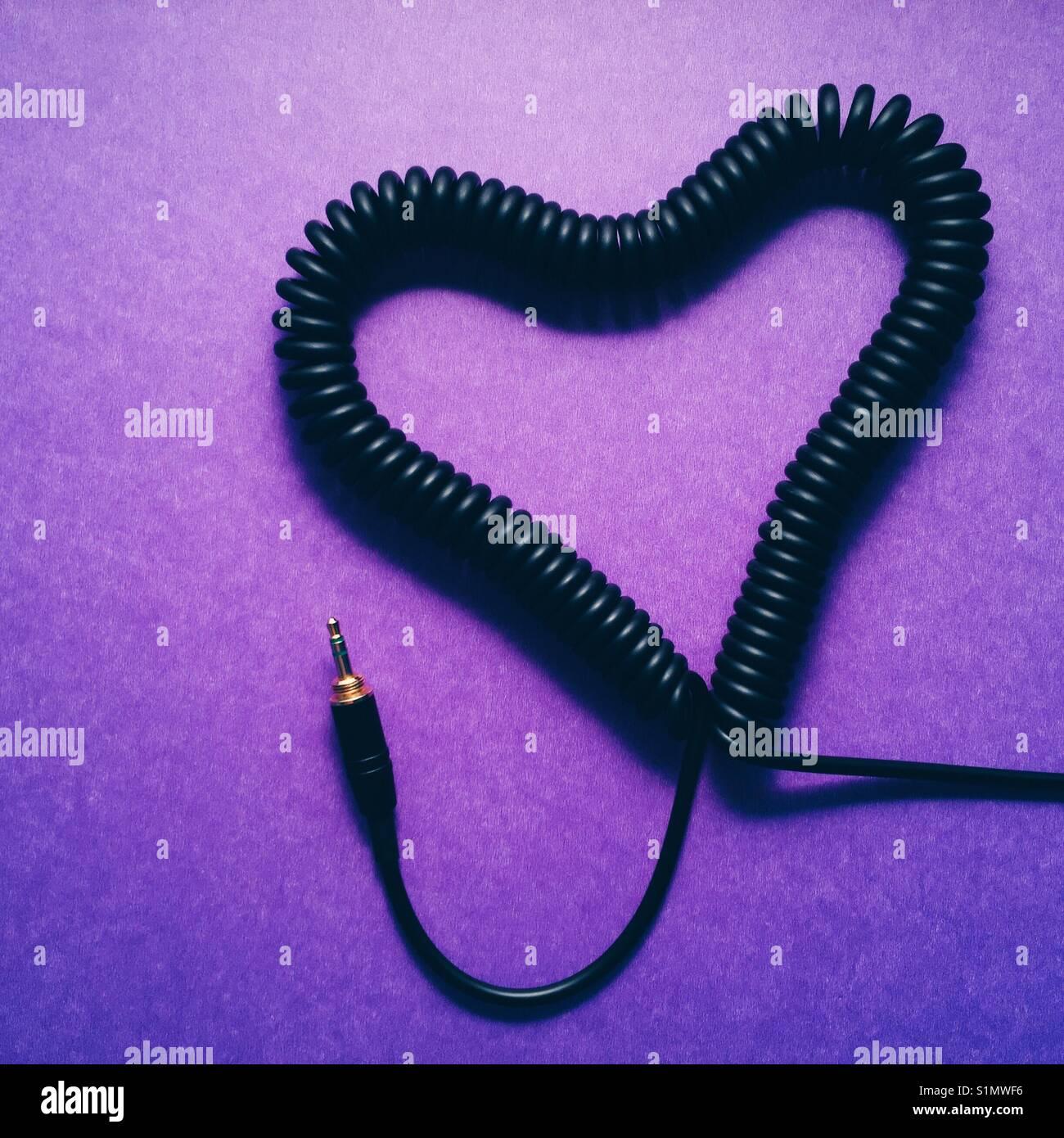 Équipé d'un câble du casque en fait à une forme de coeur sur fond violet Photo Stock