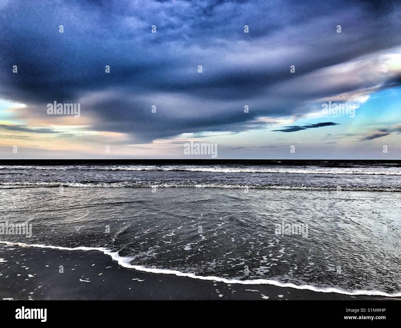 Bord de l'océan avec nuages spectaculaires au coucher du soleil Photo Stock