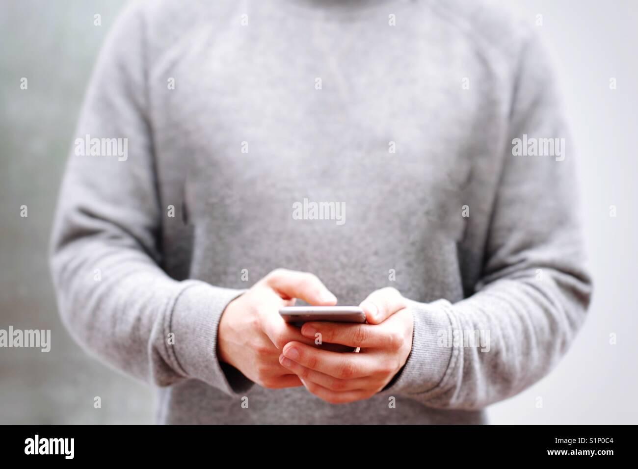 Un jeune homme hipster en gris ou argent holding up son téléphone portable tout en envoyant dans un milieu Photo Stock