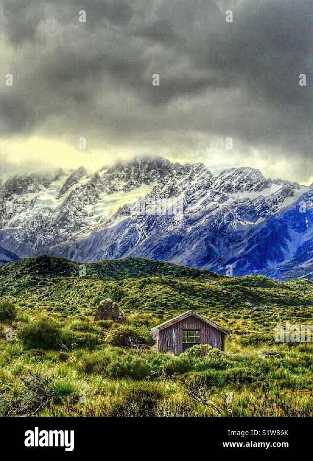 Petite hutte au pied de montagnes près de Mt Cook en Nouvelle Zélande Photo Stock