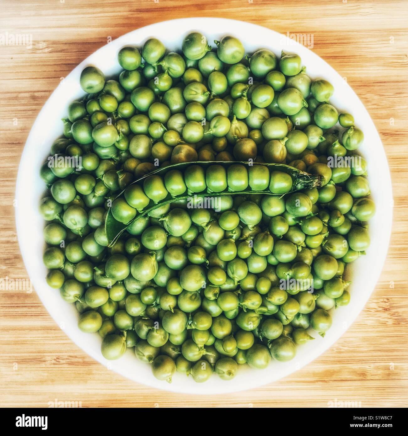 Bol de petits pois frais, et les petits pois dans une cosse, high angle view Photo Stock