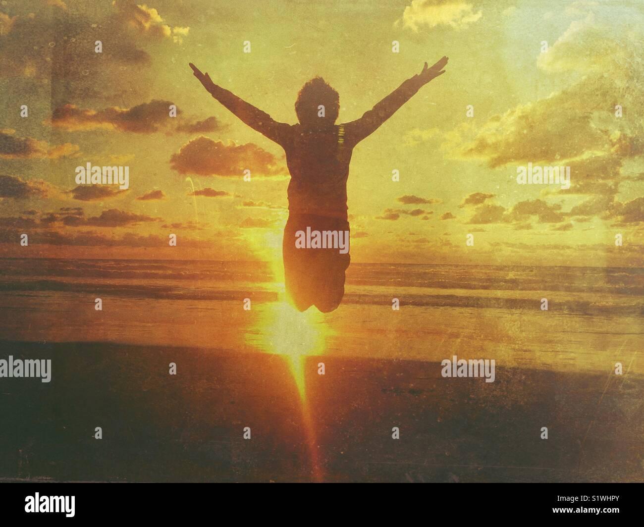 Garçon sautant avec bras tendus dans la plage au coucher du soleil Photo Stock