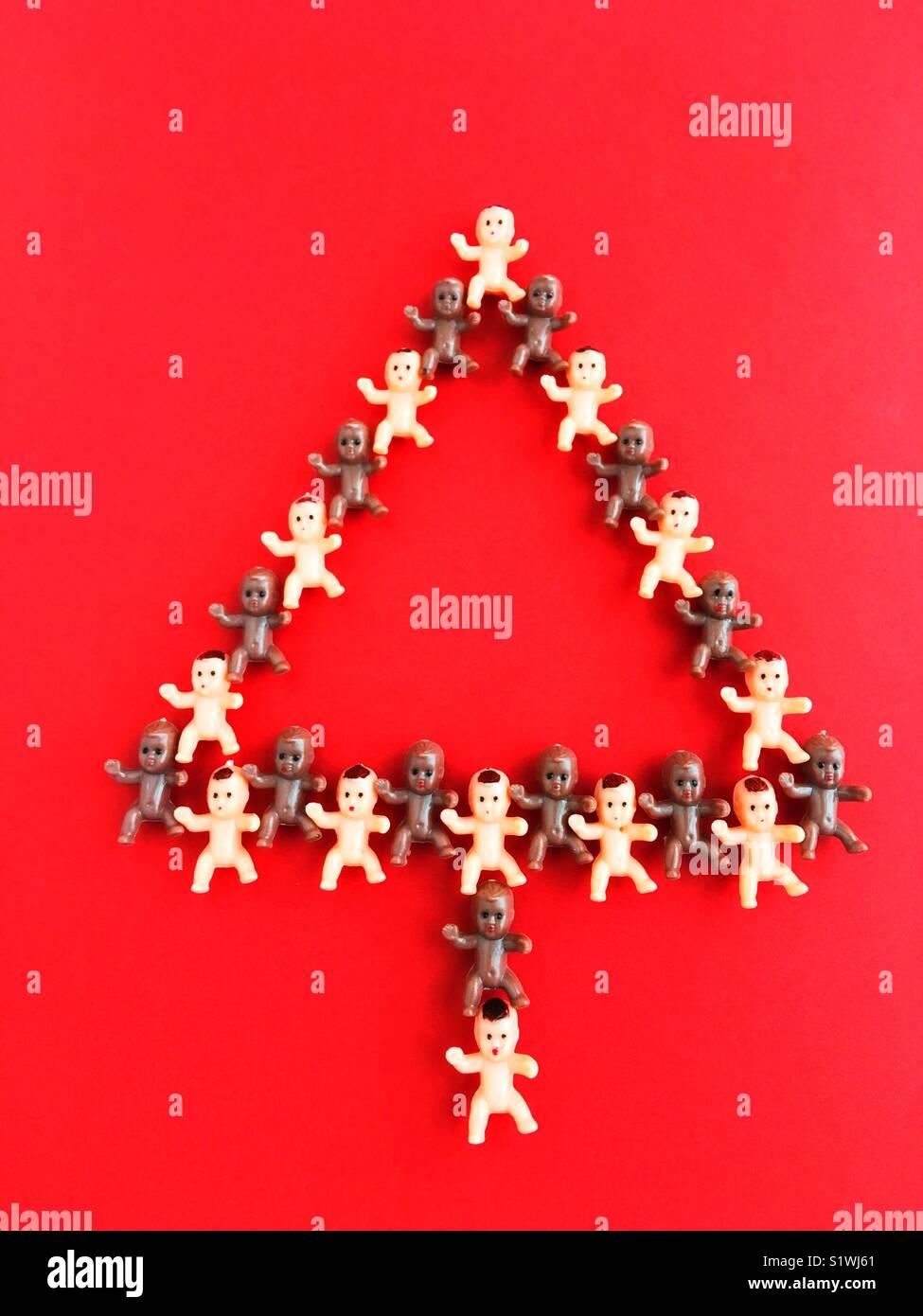 En plastique minuscules baby dolls la forme d'un arbre de Noël. Photo Stock
