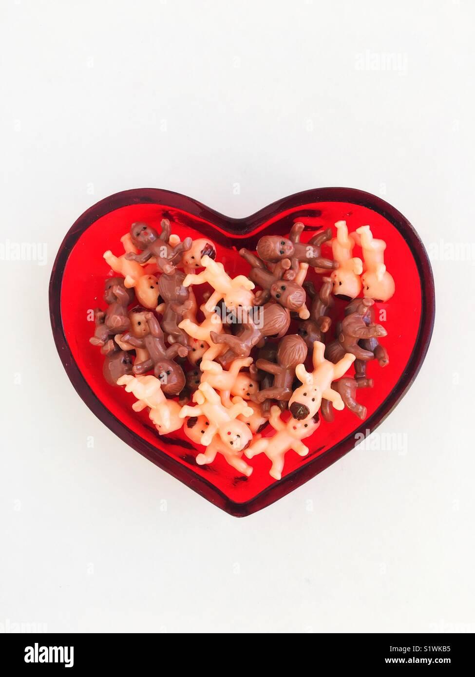 Petites Poupées en plastique dans un plat en forme de coeur. Photo Stock