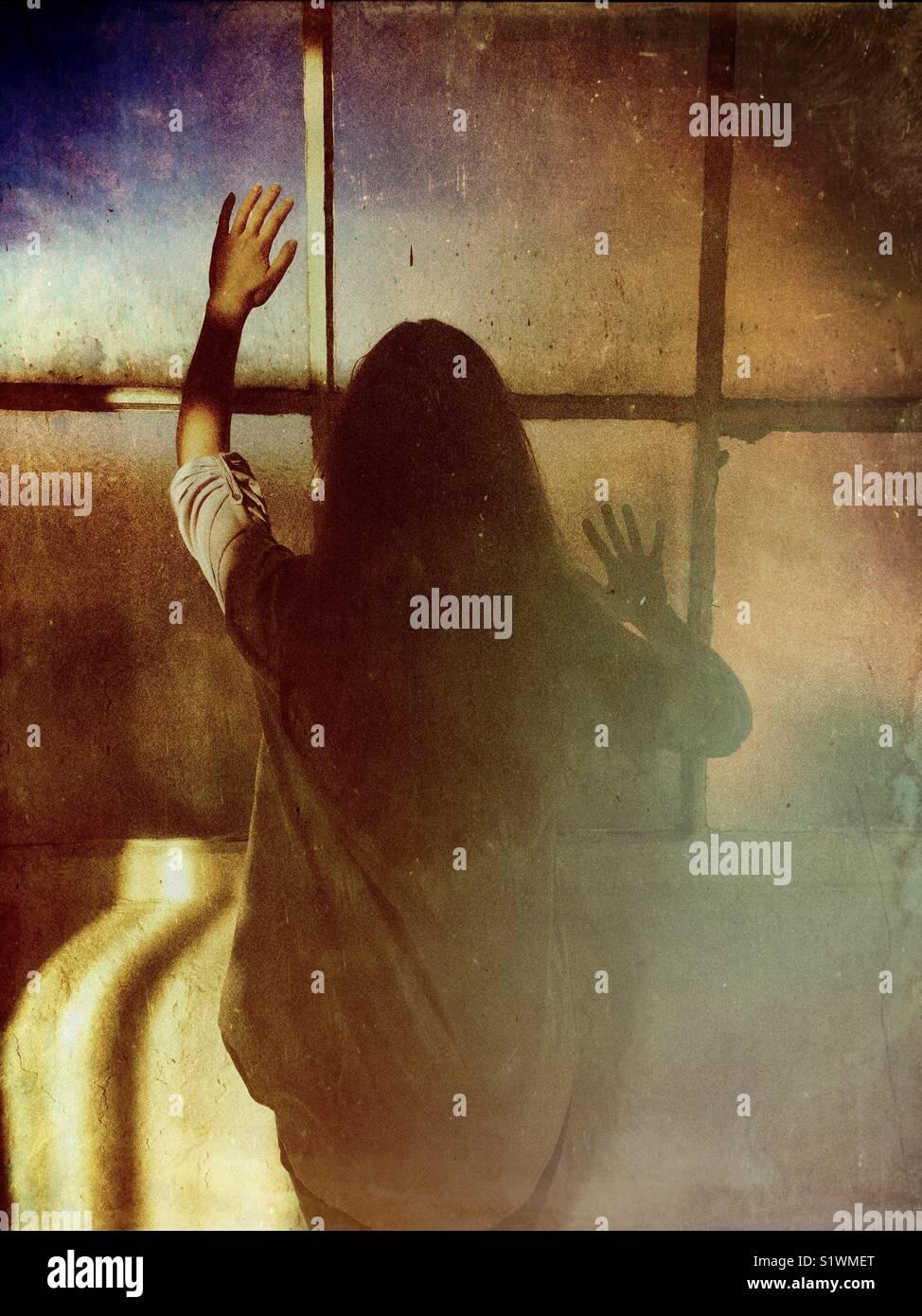 Vue arrière de la femme debout près de la fenêtre de toucher le verre à la main Photo Stock