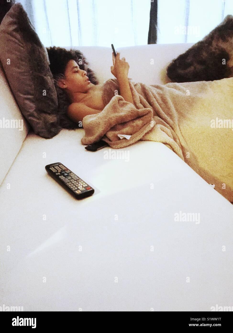 Garçon sur le canapé avec la technologie, téléphone et commande à distance Photo Stock