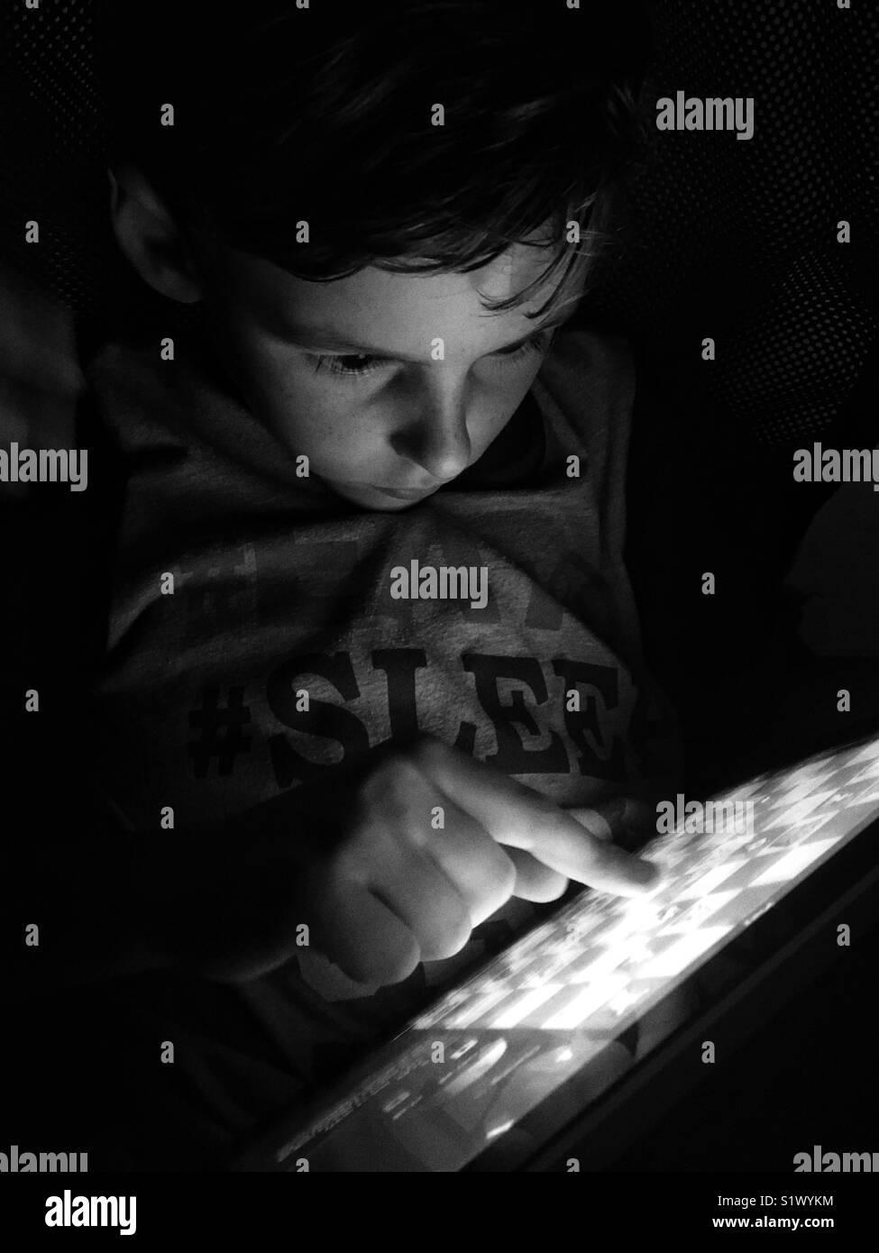 Jeune garçon jouant aux échecs sur tablette Photo Stock
