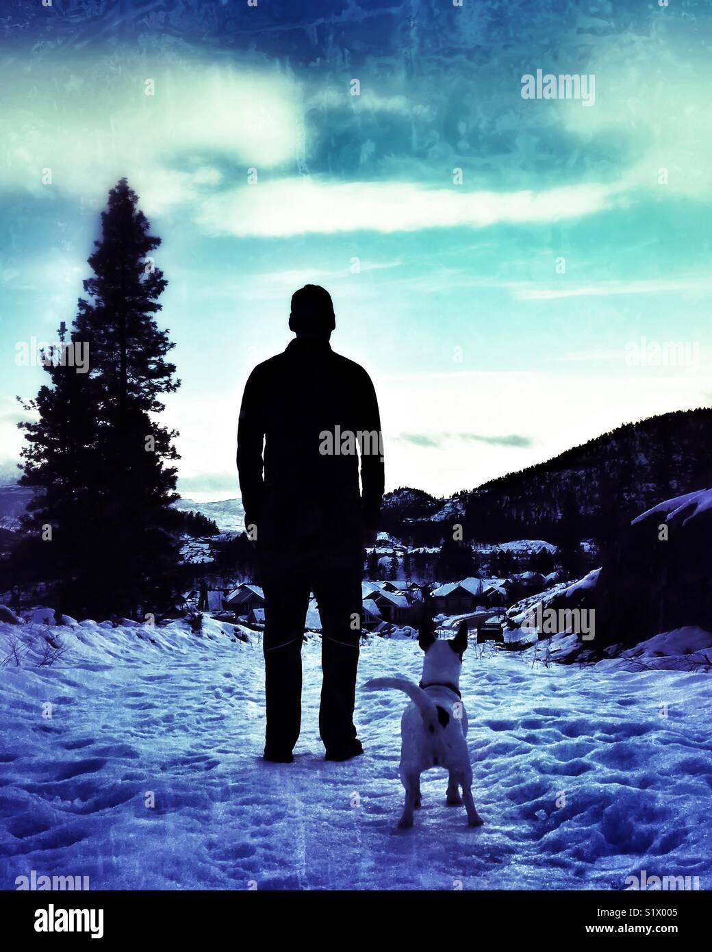 Silhouette d'un homme debout dans la neige avec son chien. Photo Stock