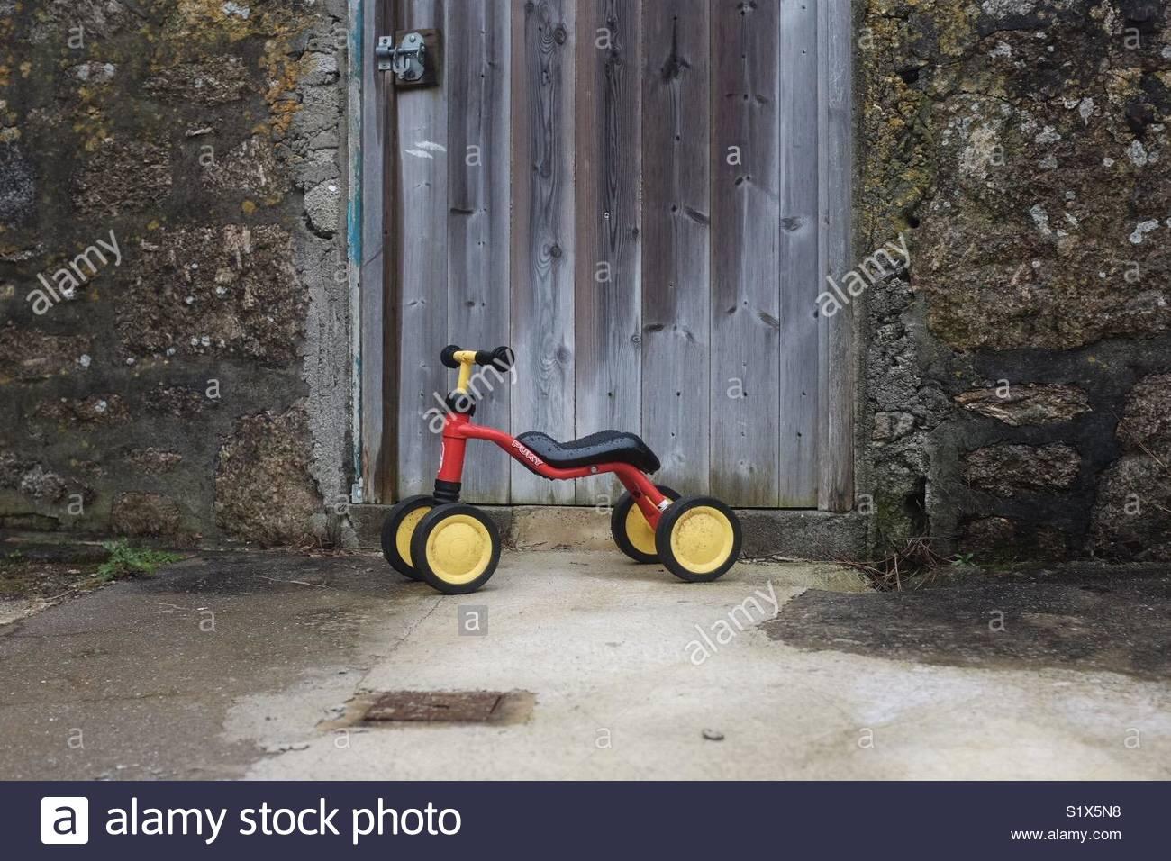 Tricycle enfant contre weathered barn door entouré de mur vieilli Photo Stock