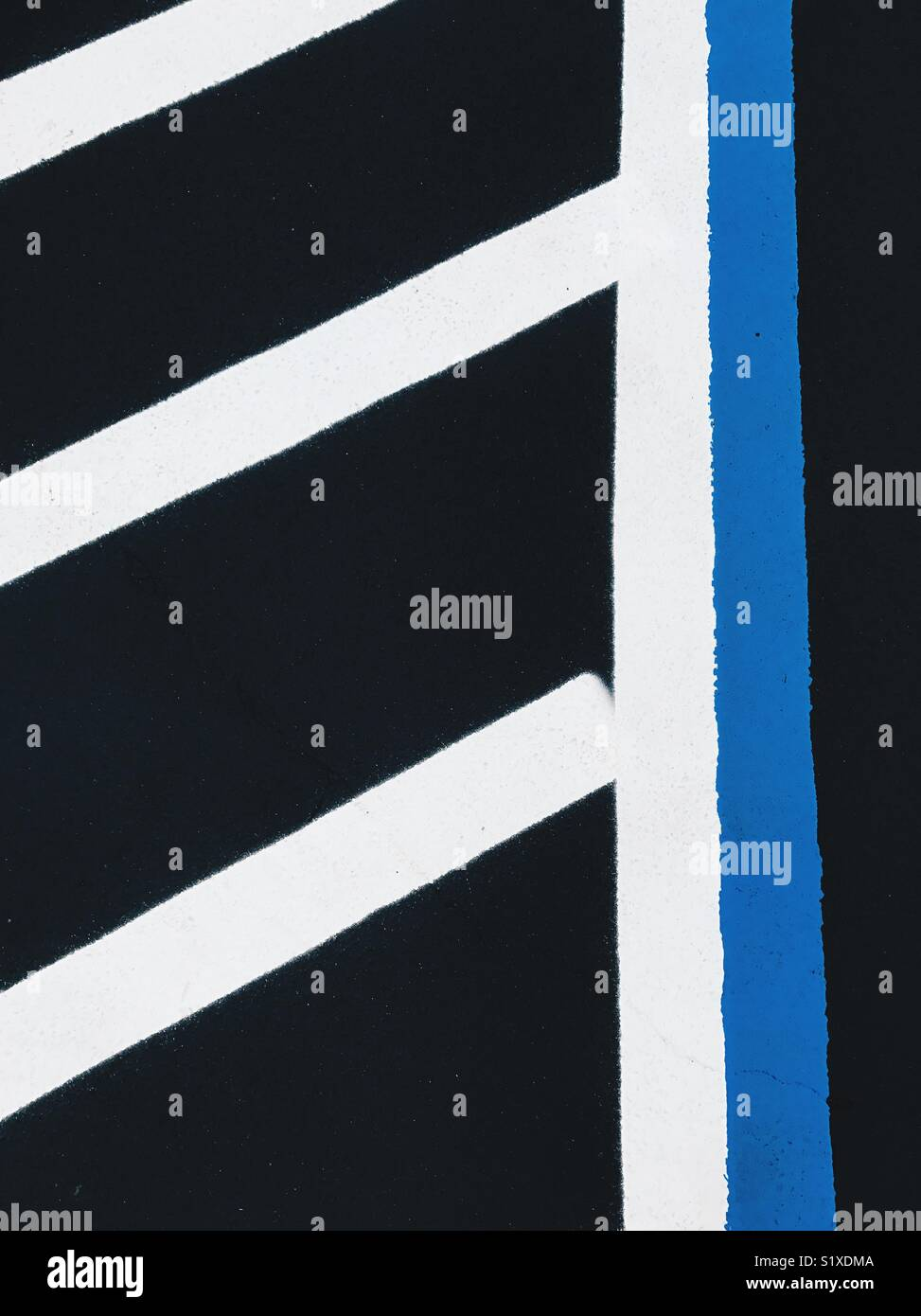 Bold peint en blanc et bleu sur les lignes d'asphalte noir dans un parking. Photo Stock