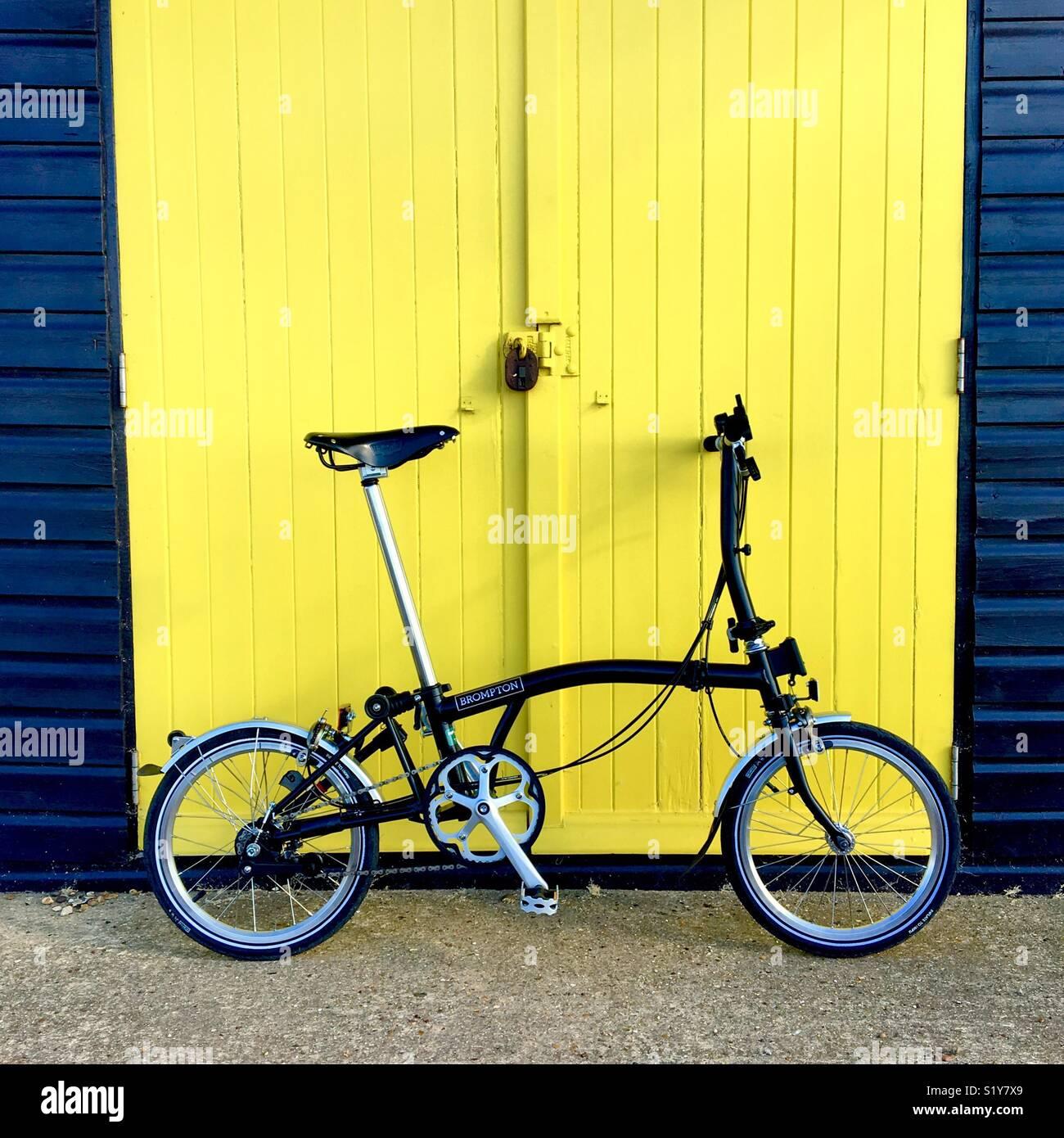 Un vélo Brompton noire appuyée sur une cabane de plage peint jaune porte. Photo Stock