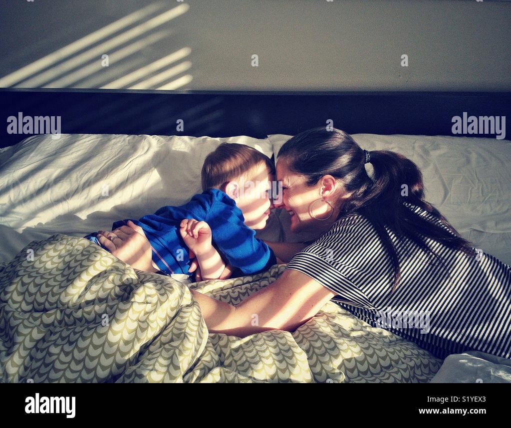 La mère et le fils dans le lit dans la lumière du soleil Photo Stock