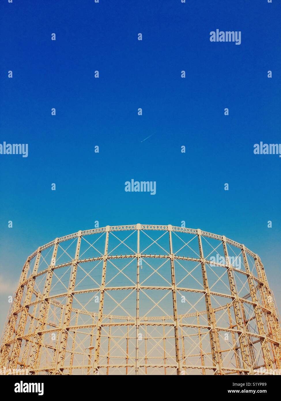 Charpente du gazomètre vide contre un ciel bleu vif avec jet et traînée Photo Stock