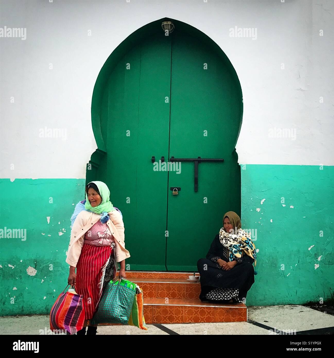 Les femmes marocaines s'asseoir en face d'une porte verte à Tanger, Maroc, Afrique Photo Stock
