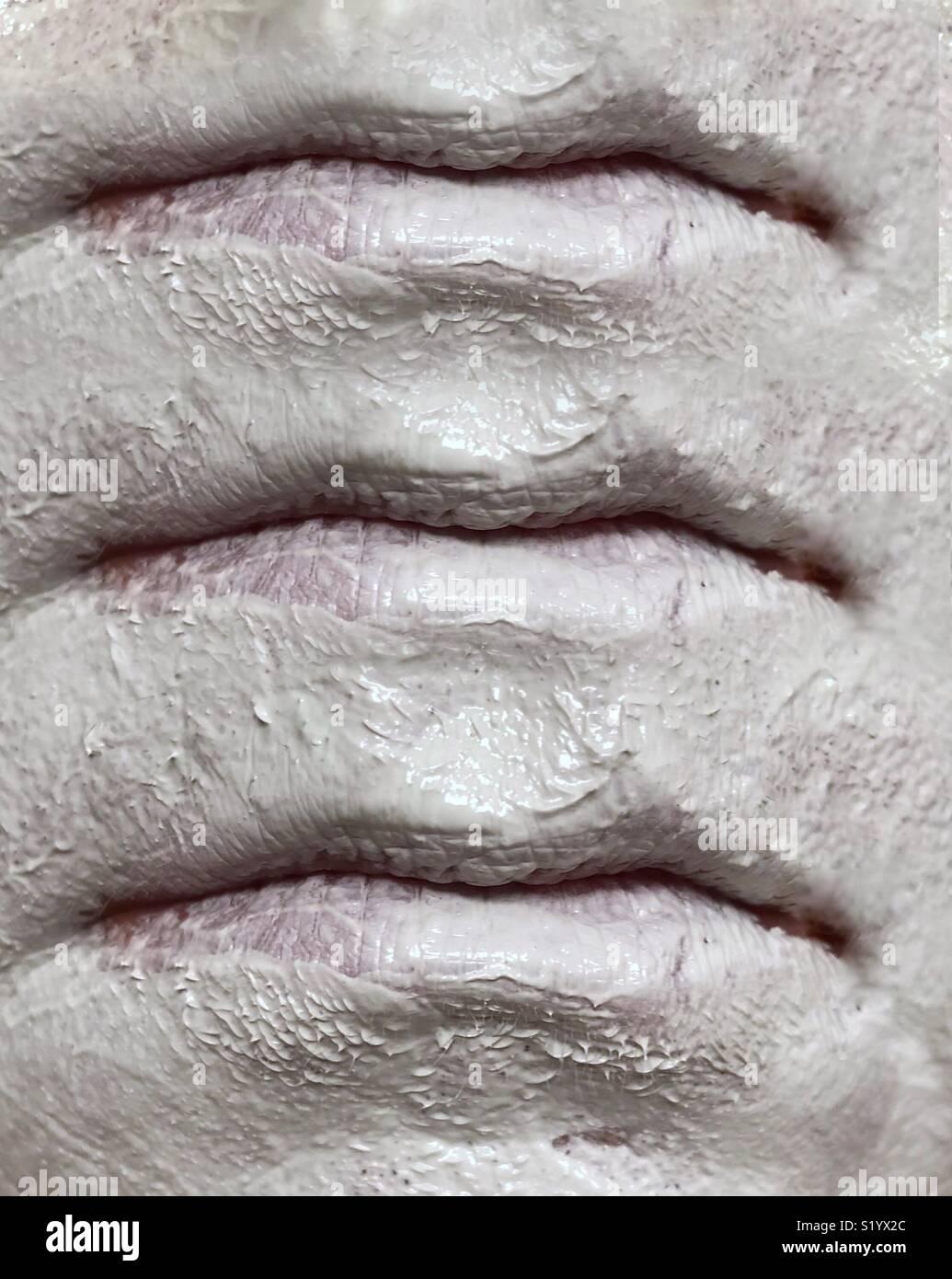 Une image abstraite de trois ensembles de lèvres, sur un visage portant un masque de boue argile blanche Photo Stock