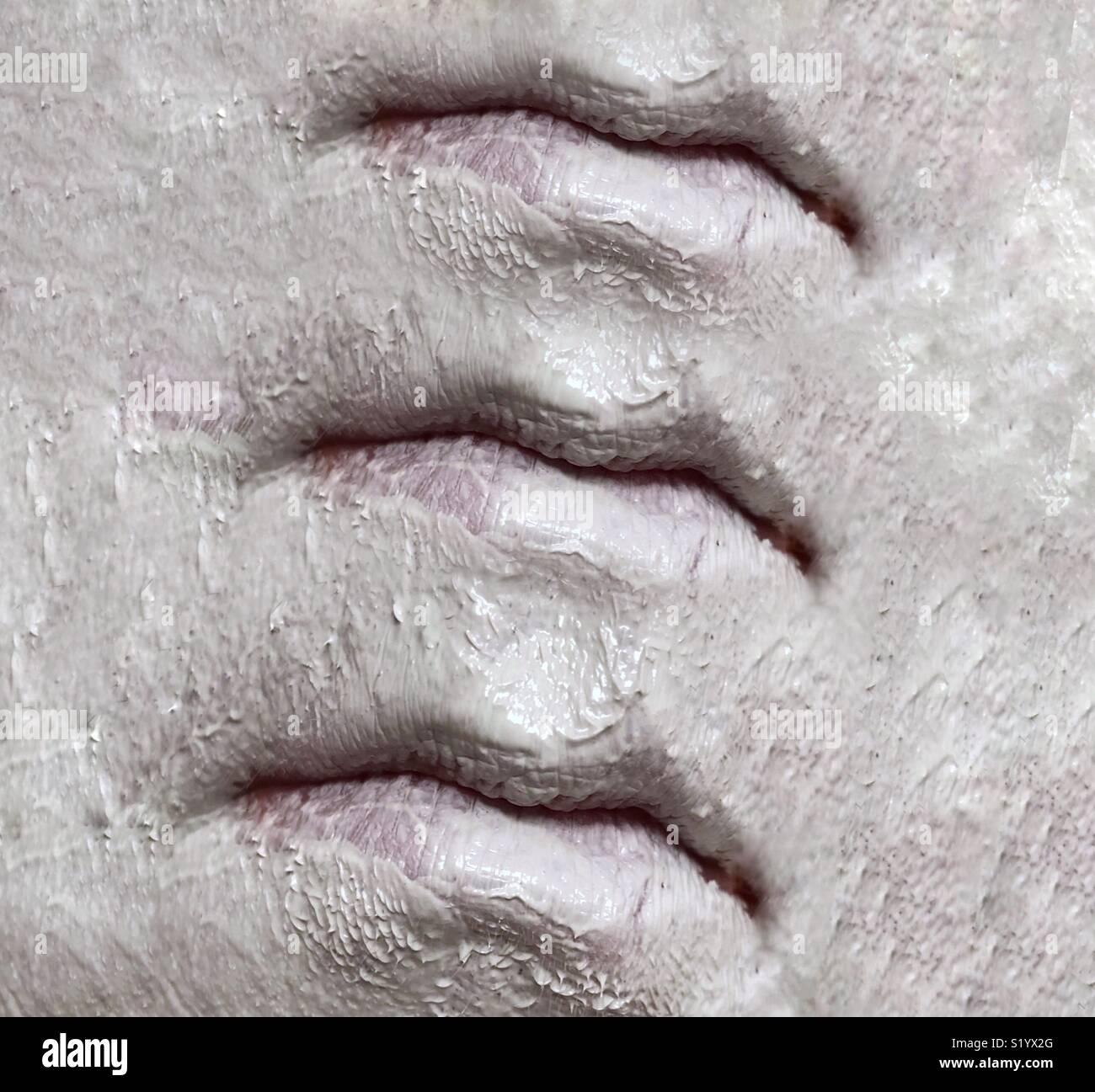 Une image abstraite de trois ensembles de lèvres sur un visage recouvert d'un masque de boue argile blanche Photo Stock