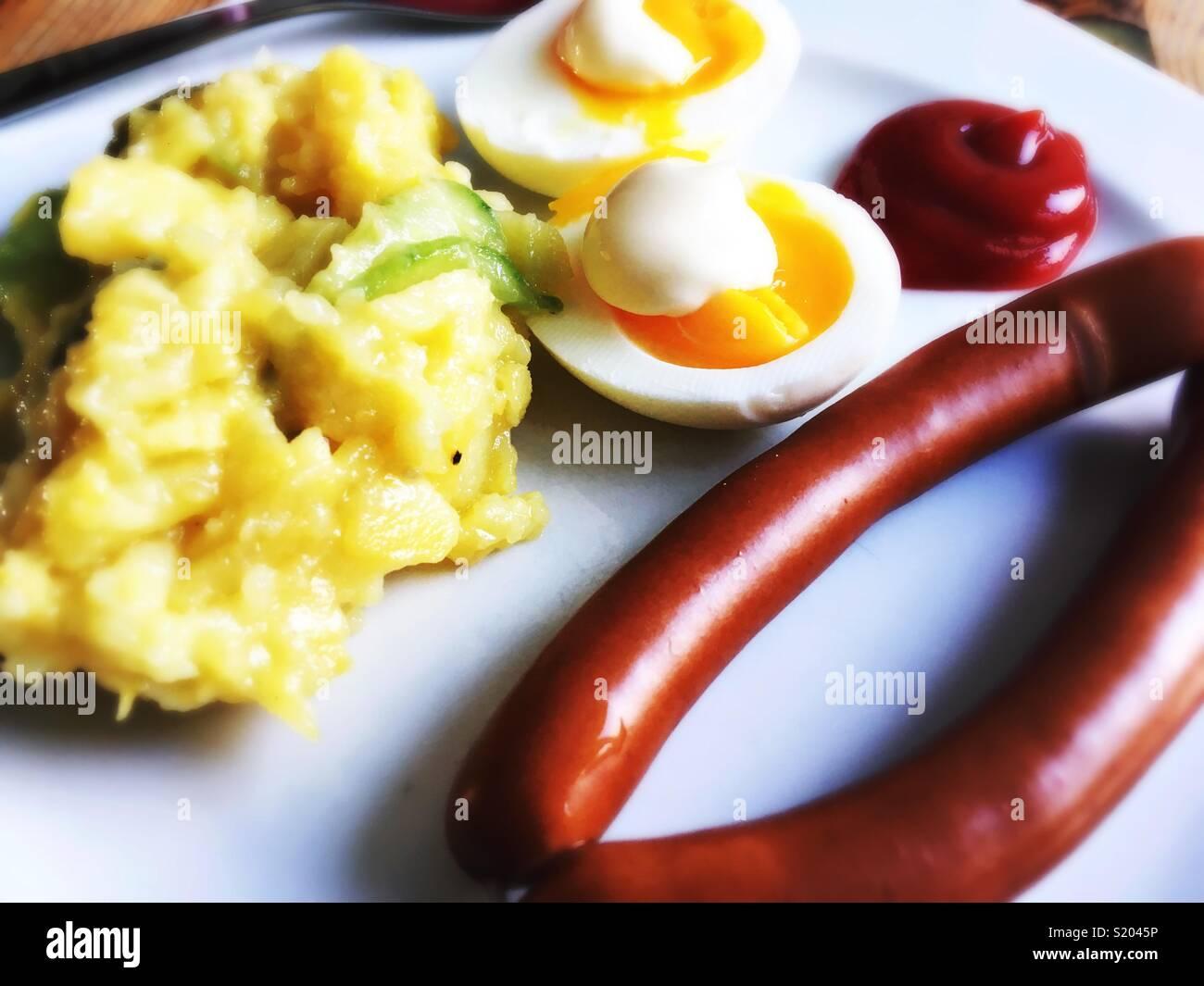 Une paire de saucisses de Vienne, oeufs, mayonnaise, ketchup et salade de pommes de terre sur une plaque blanche Photo Stock