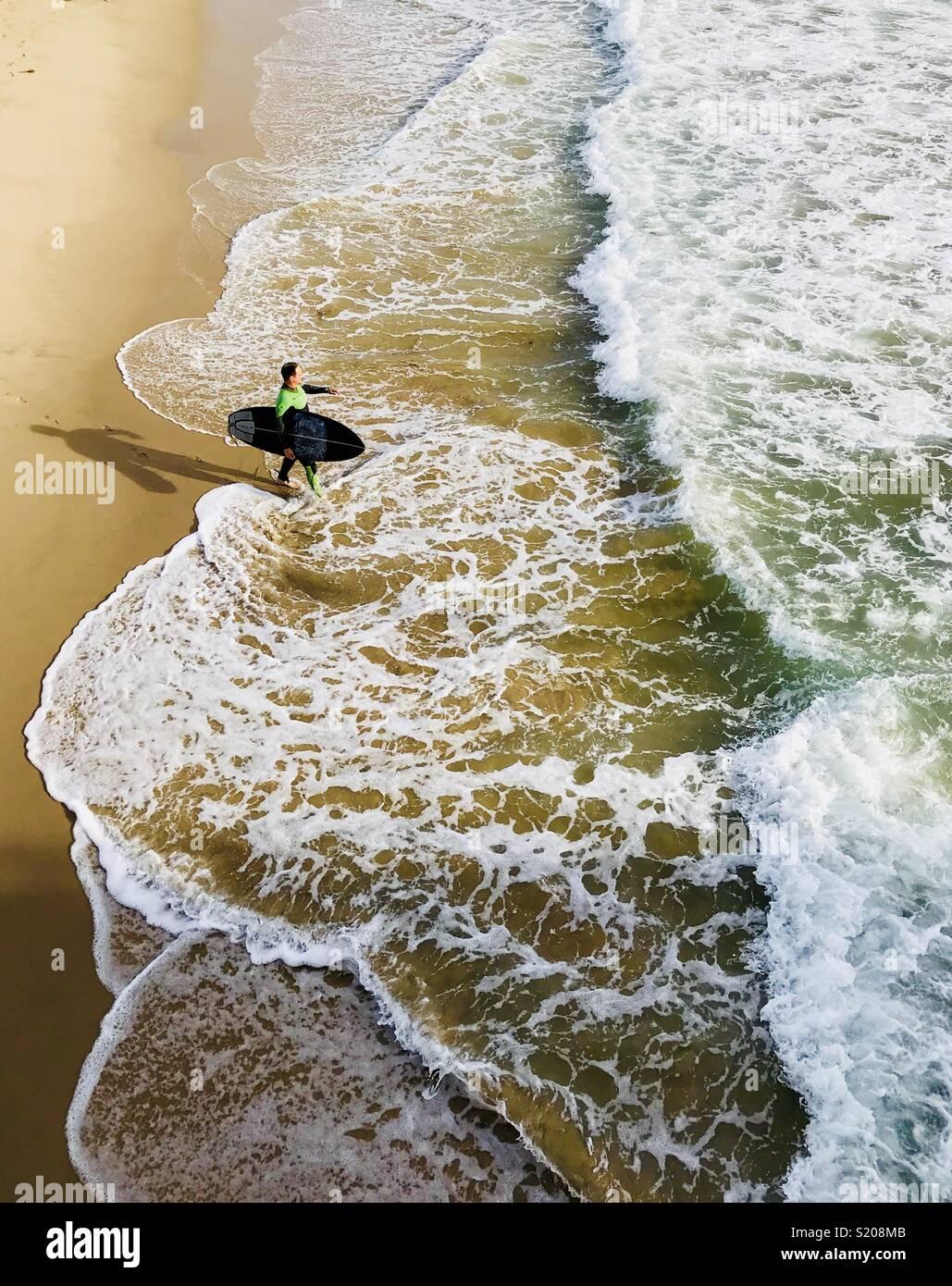 Un homme marche sur le surfeur surf. Manhattan Beach, Californie, États-Unis. Banque D'Images