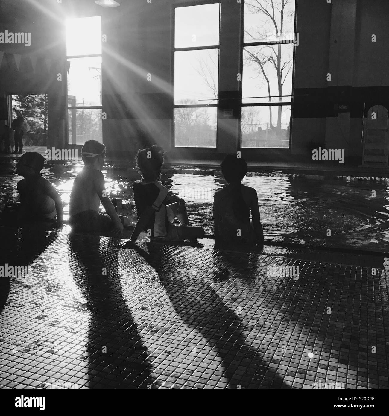4 enfants à la piscine intérieure en hiver. Photo Stock