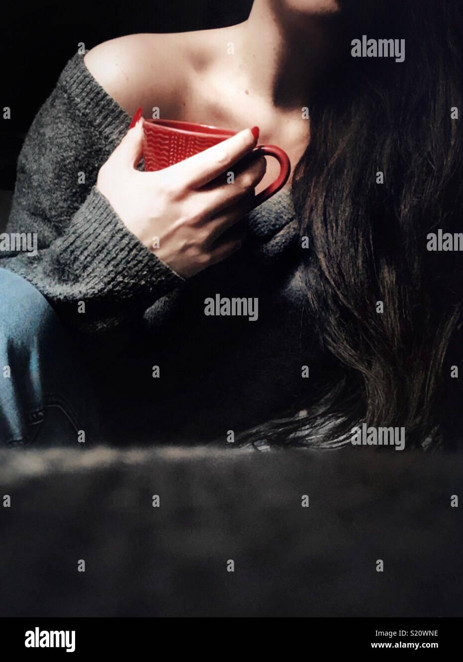 Femme avec de longs cheveux noirs tenant une tasse rouge Photo Stock