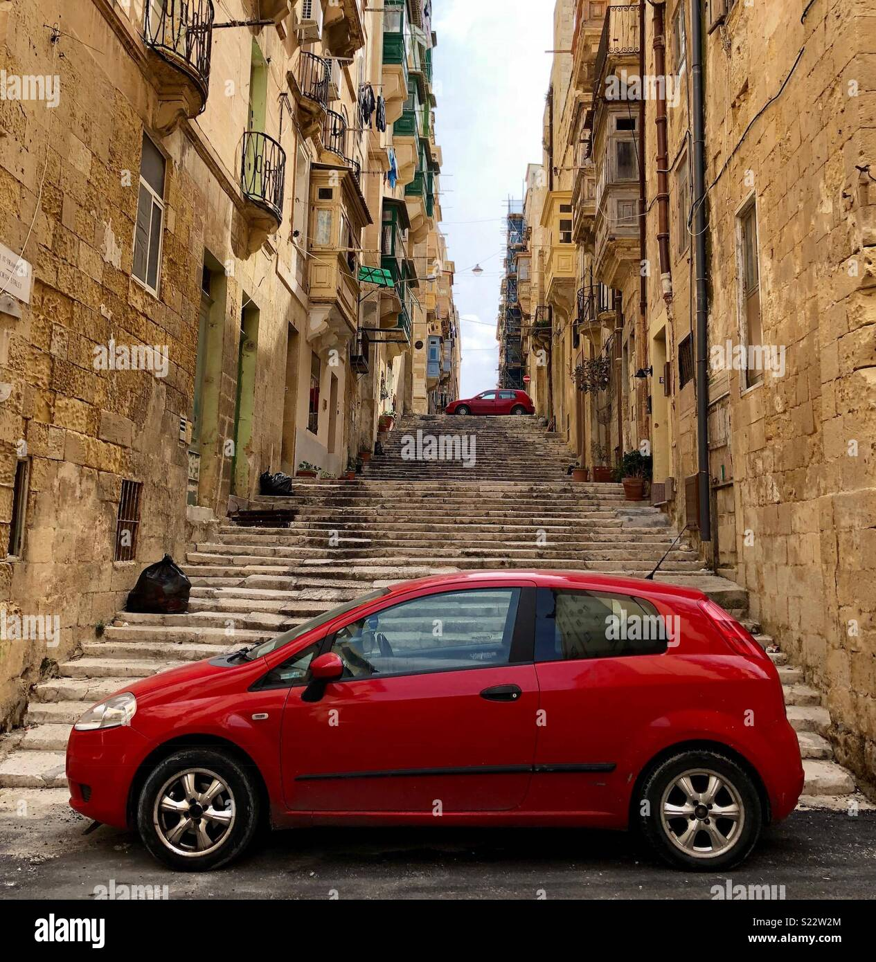 La rue longue avec des voitures rouges - une dans la distance et l'un à l'avant-plan Photo Stock