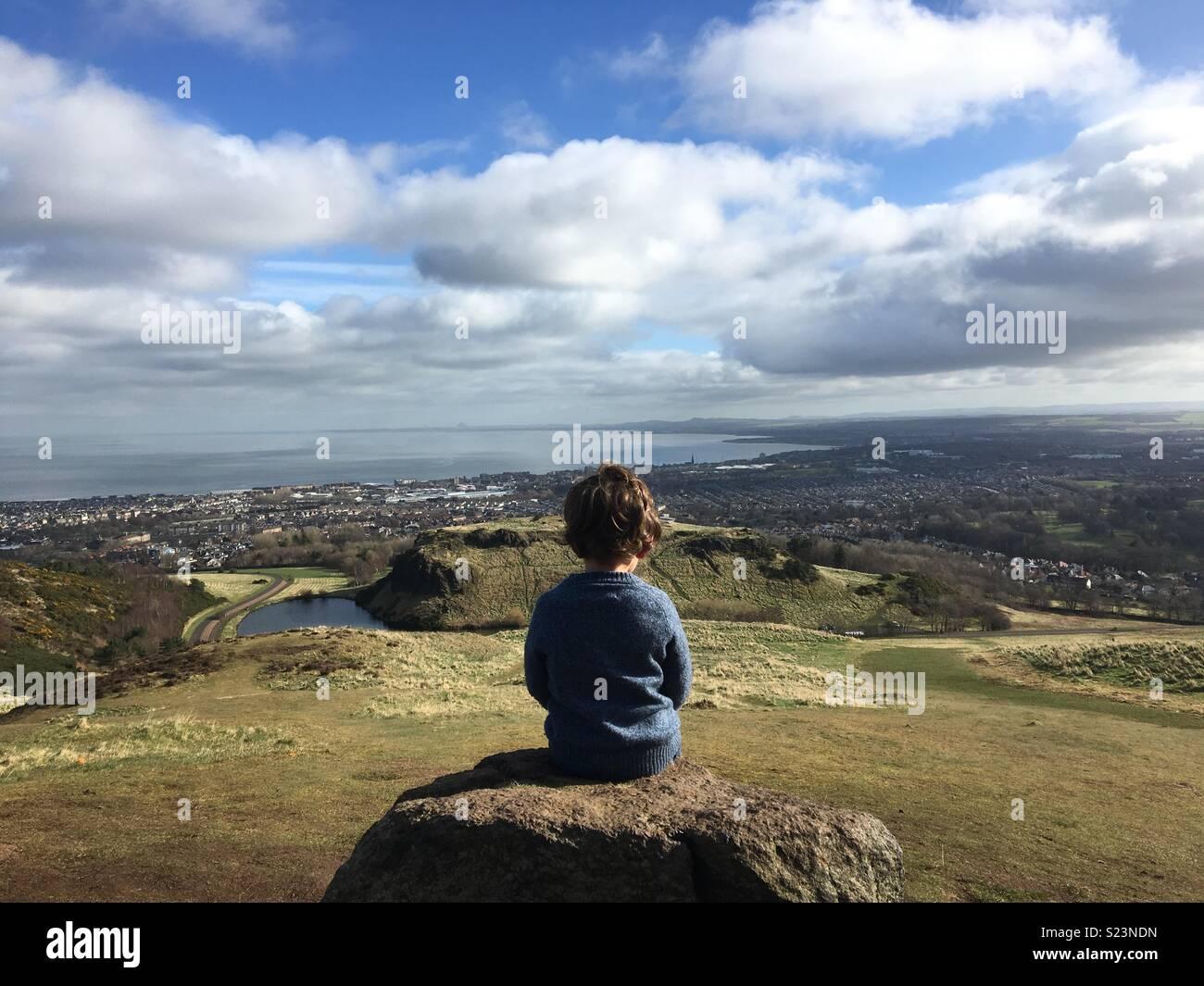 Garçon assis sur le siège d'Arthur, Édimbourg Photo Stock