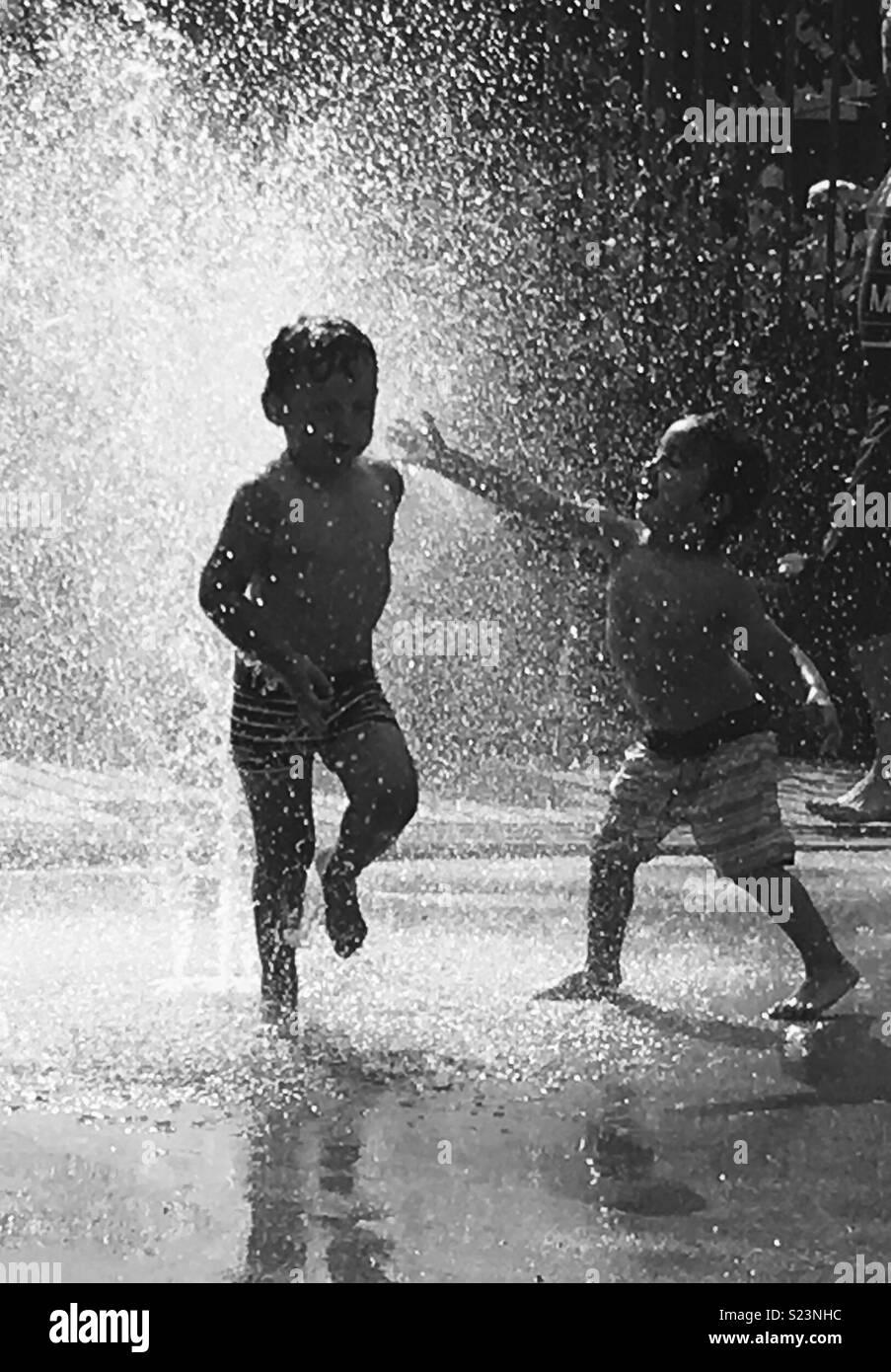 Les enfants s'amusant dans la fontaine au cours de chaude journée d'été Photo Stock