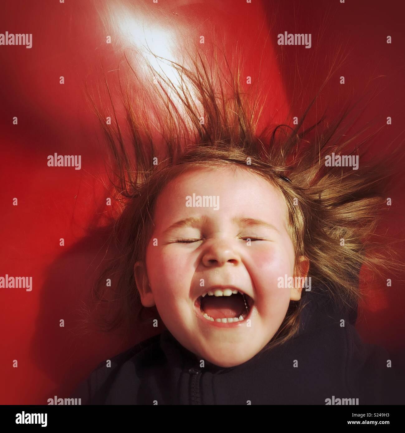 Bébé fille rire avec joie comme elle glisse vers le bas une diapositive rouge Photo Stock
