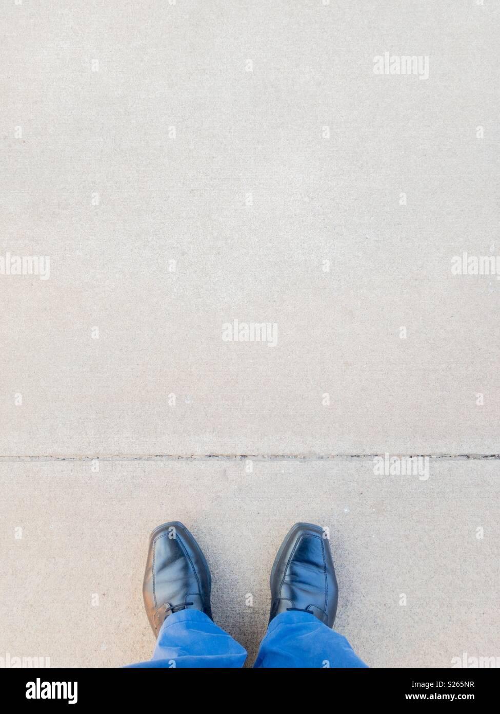 Point de vue personnel d'un homme debout en face d'une ligne tracée sur le sol. Photo Stock
