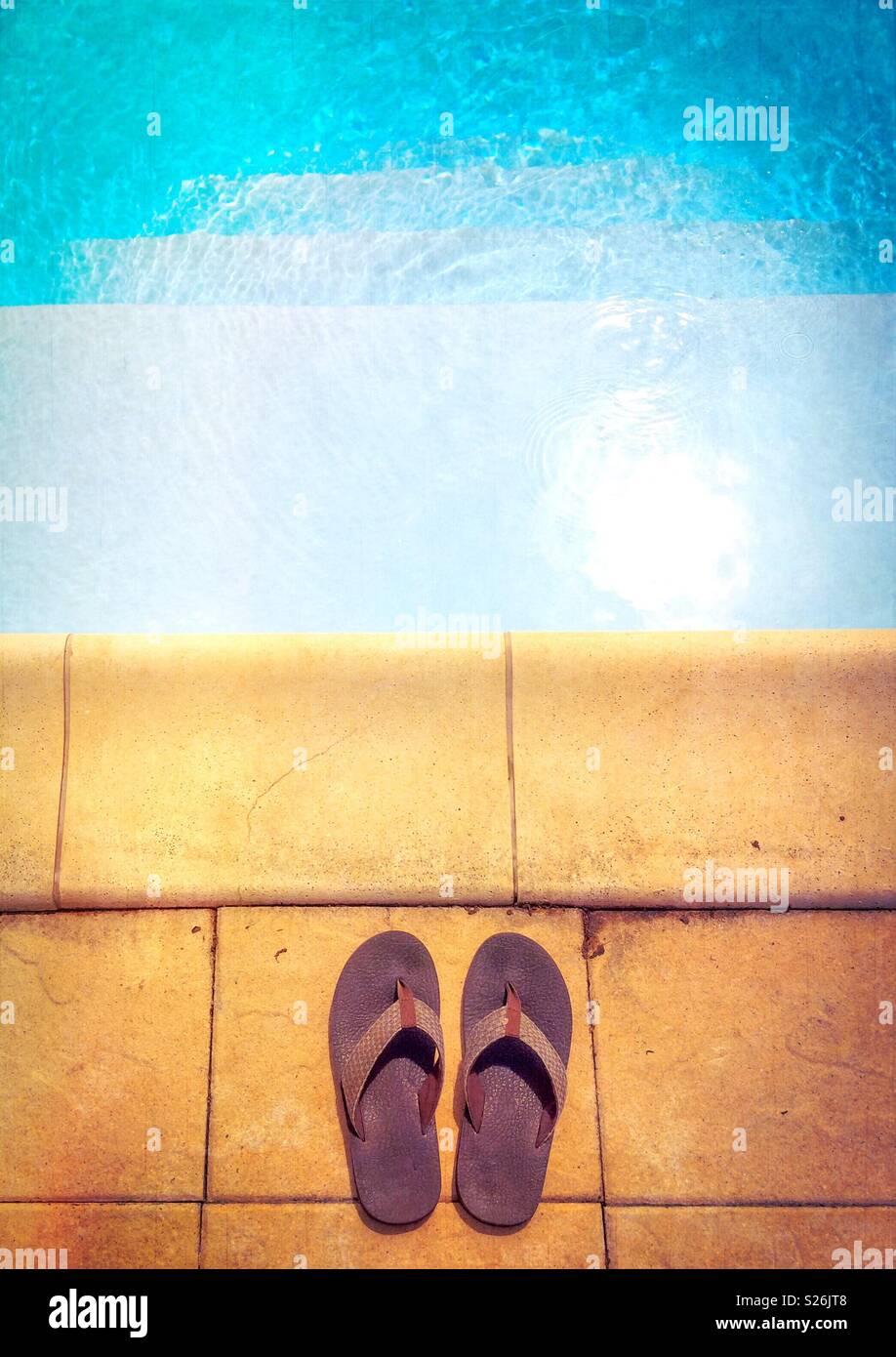 Entrer dans la piscine. Mise à plat photo d'une paire de tongs sur le bord d'une piscine. Concept d'été. Photo Stock