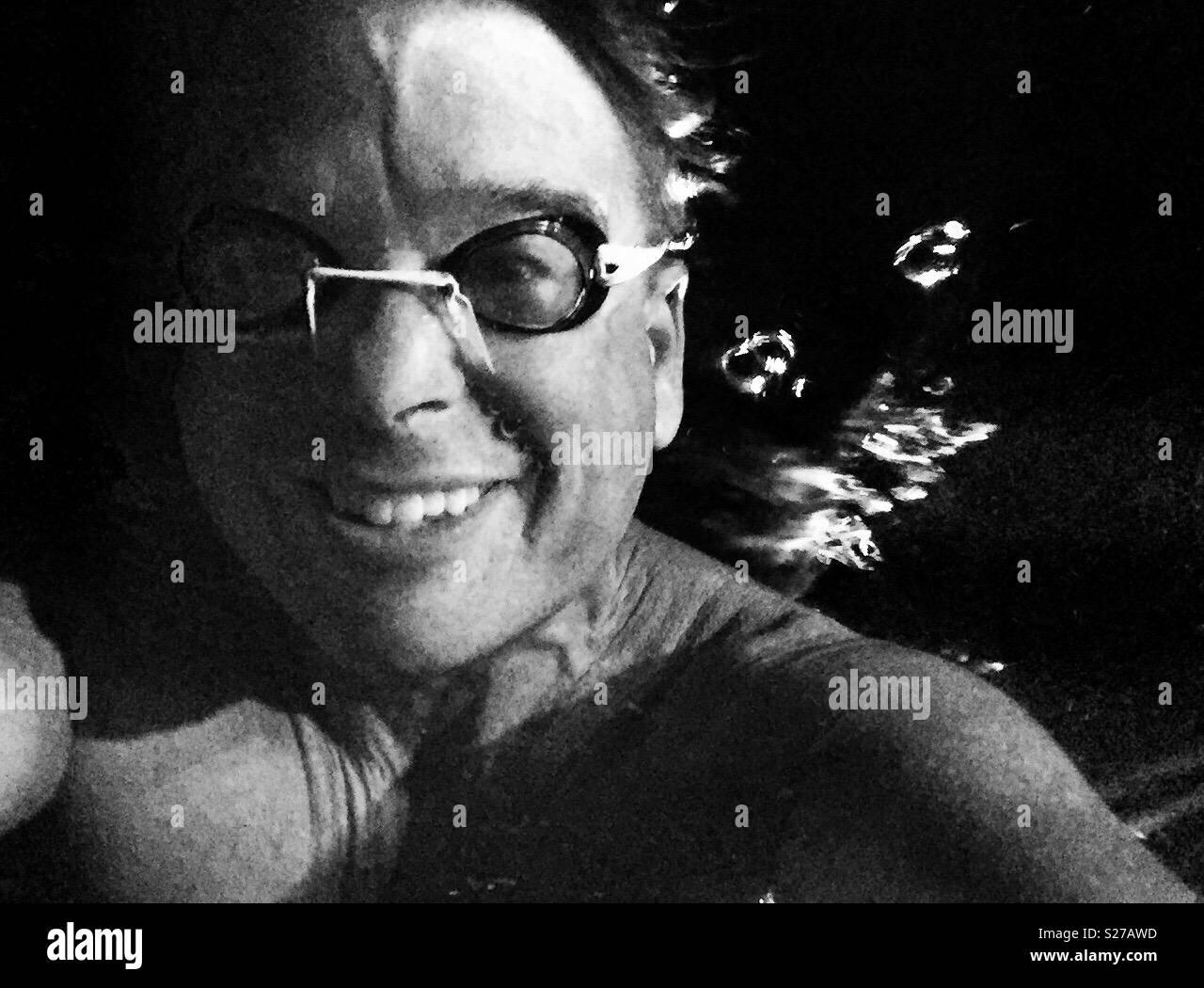 Souriante jeune nageur avec lunettes déjà sous l'eau dans la piscine avec bulles émanant de derrière Photo Stock