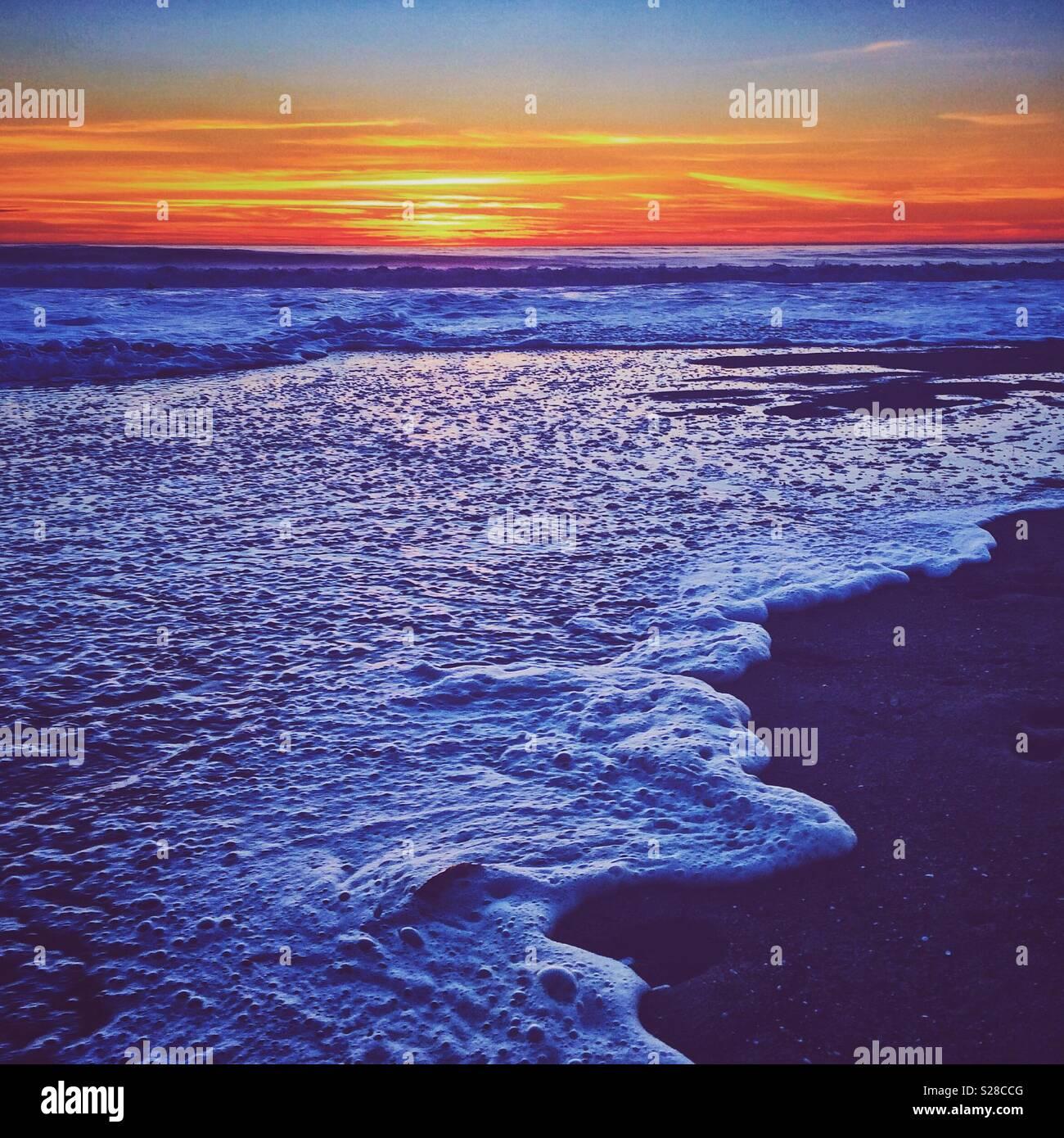 Les vagues déferlent sur la plage au coucher du soleil à El Porto, Californie près de Manhattan Beach Banque D'Images