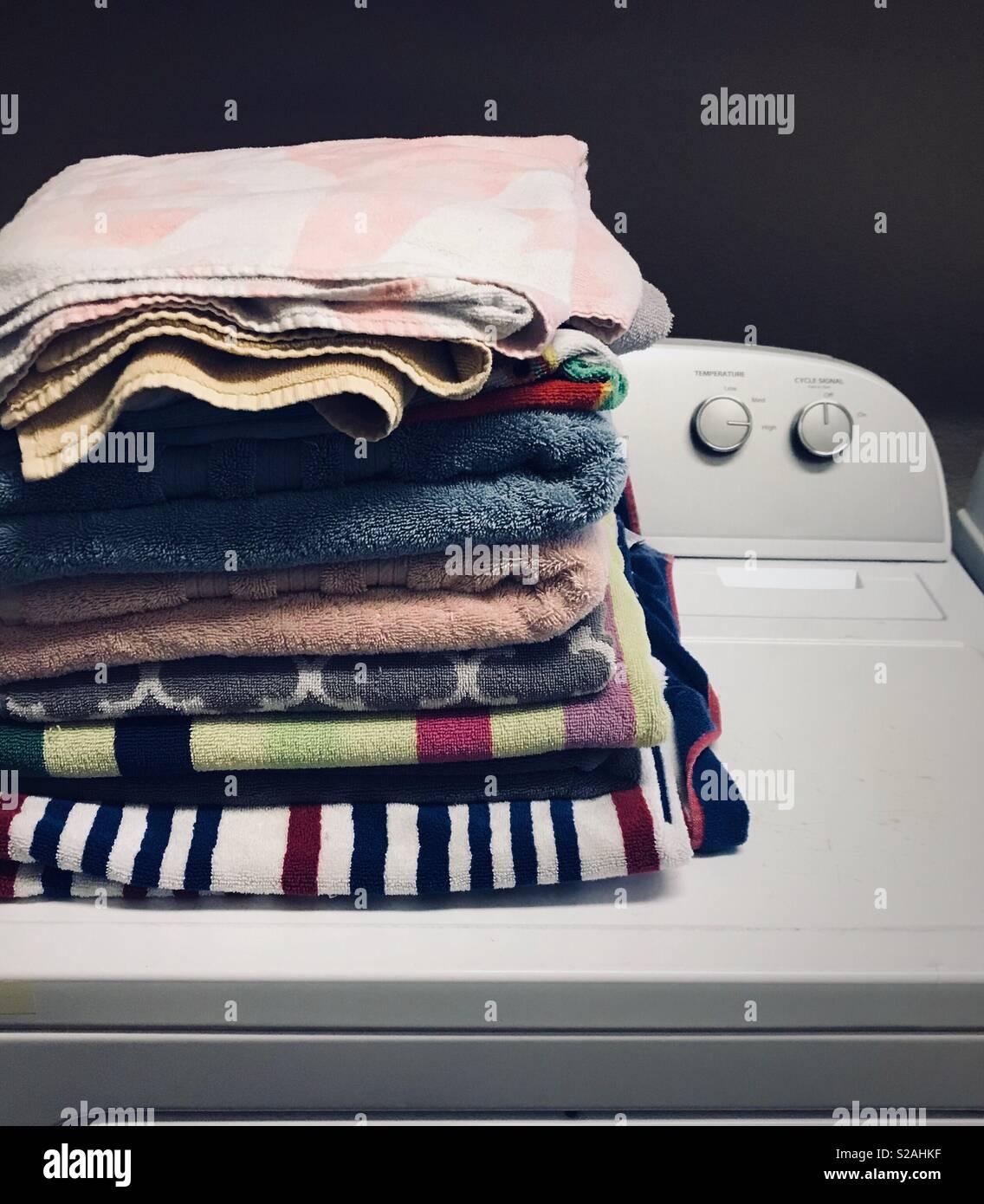 Serviettes pliées colorés assis sur le dessus du sécheur corvées maison - Accueil - La vie de vêtements- serviettes pliage Photo Stock