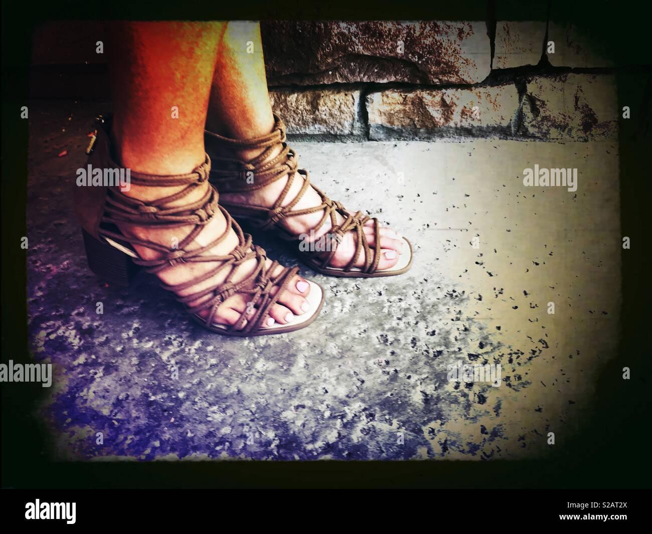 Femme portant à lanières marron léger Gladiator Sandals dehors sur la terrasse sur une chaude journée d'été Banque D'Images