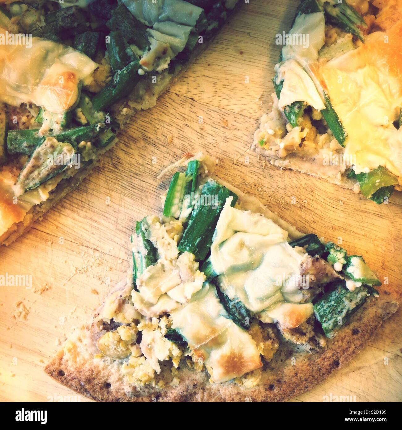 Des tranches de régime sans gluten Sans lactose végétalien végétarien pizza blanche sur une planche à découper en bambou. L'okra, pois chiches, mozzarella vegan. Faible taux de cholestérol sain coeur contemporaine. Photo Stock