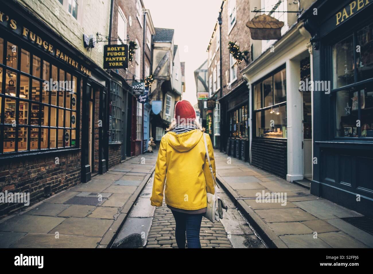 Une vue arrière d'une jeune fille à la mode de porter un manteau jaune et marcher le long d'une rue commerçante médiévale et historique connu sous le nom de York Shambles, UK Banque D'Images