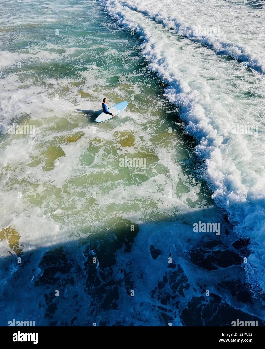 Un homme marche sur le surfeur surf. Manhattan Beach, California USA Banque D'Images