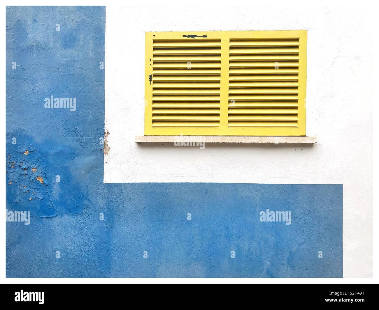 Volets jaune sur une fenêtre entourée d'un mur peint en bleu un blanc Photo Stock